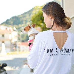 kobieta z psem na rękach ubrana w białą bluzkę z wycięciem na plecach