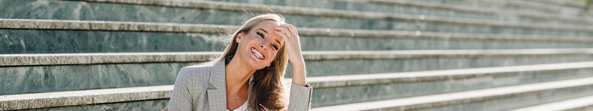 Młoda kobieta siedząca na schodach uśmiechająca się