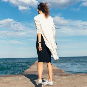Kobieta w swetrze stojąca na molo