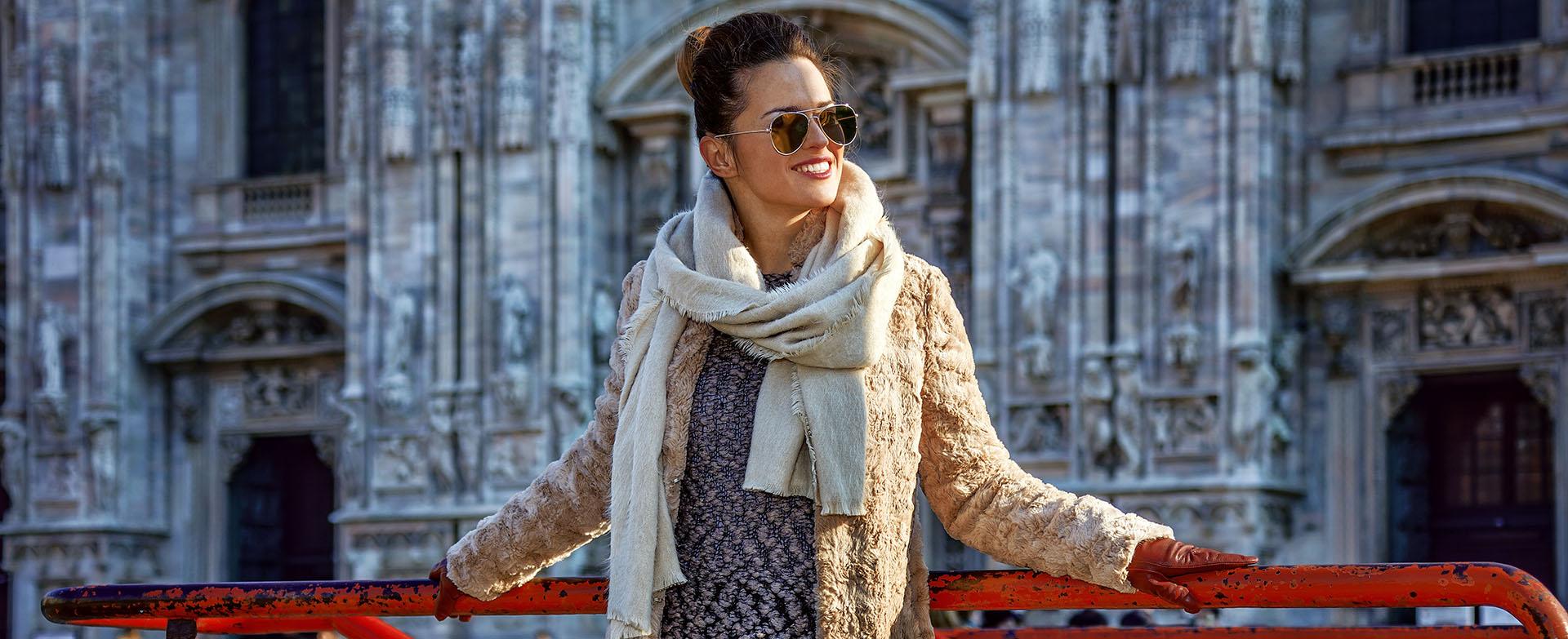 Kobieta w płaszczu w mieście przed zabytkową budowlą